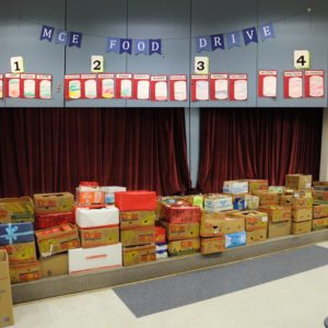 Stacked boxes in school cafeteria during food drive.